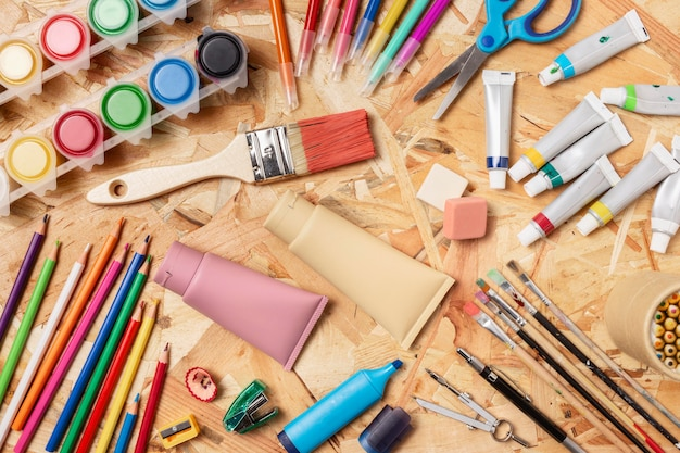 Vista superior variedade de tintas e lápis