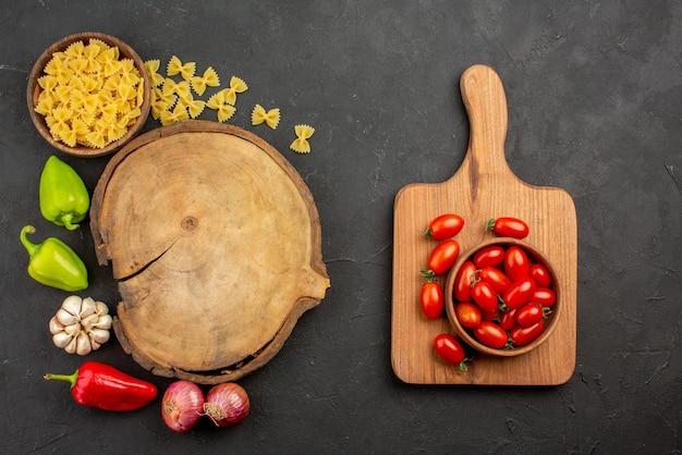 Vista superior vegetais apetitosos pimentão cebola macarrão alho em torno da tábua de corte ao lado da tigela de tomates na tábua de madeira