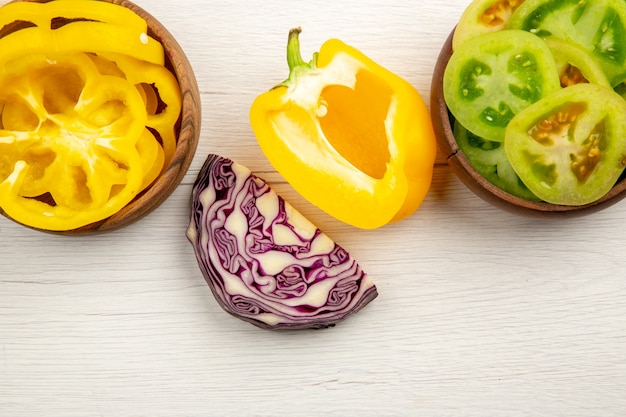 Vista superior vegetais frescos cortados verdes tomates pimentão amarelo em tigelas repolho roxo na superfície de madeira branca