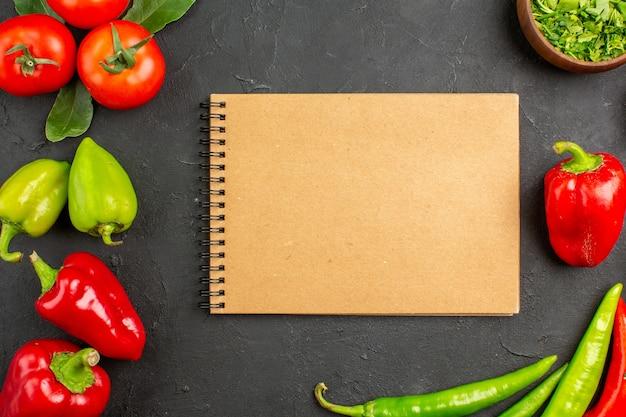Vista superior, vegetais frescos, tomates e pimentões na salada de piso escuro, cor de refeição madura