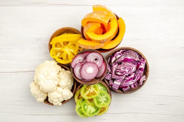 Vista superior vegetais picados cortados repolho roxo corte abóbora pimentões amarelos cortados cebola tomate verde couve-flor em tigelas na superfície branca