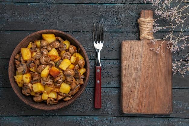Vista superior vegetal com cogumelos, batatas e cogumelos na tigela ao lado do garfo e a tábua de cortar na mesa escura