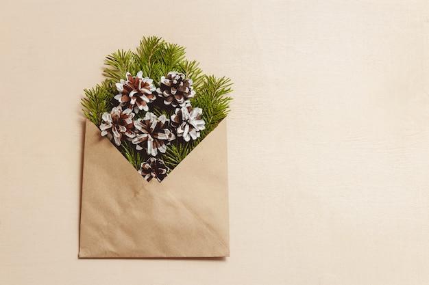 Vista superior verde abeto galhos e cones em envelope artesanal marrom