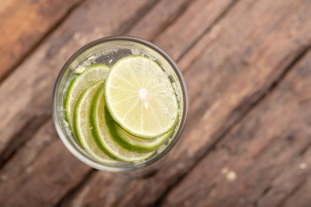 Vista superior verde limão fatiado na água com gás e copo de lugar na mesa de madeira