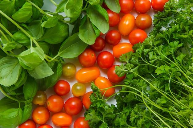 Vista superior verdes com tomates na superfície branca. horizontal