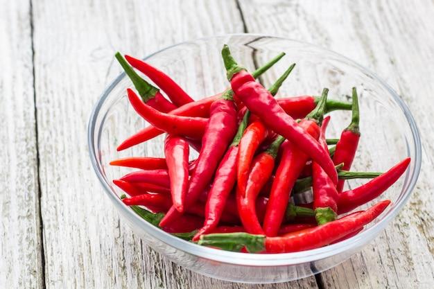 Vista superior, vermelho, chilli peppers, em, tigela transparente, branco, madeira