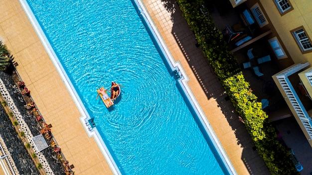 Vista superior vertical da piscina em hotel residência de férias com pessoas adulto sênior deitar e desfrutar com colchão inflável lilos na água azul