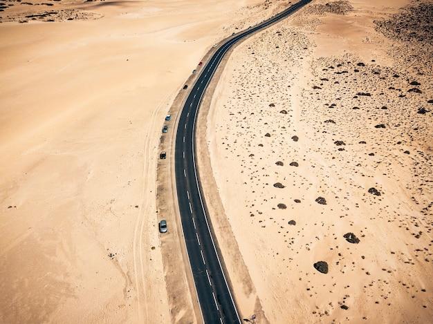 Vista superior vertical de uma estrada de asfalto preto longa e bonita cruzando o conceito de viagem de dunas de areia do deserto e lugar cênico de mudança climática árida alternativa