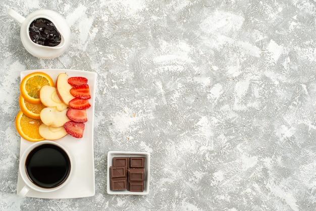 Vista superior xícara de café com geléia fatiada, maçãs, laranjas e morangos na luz de fundo branco frutas maduras frescas maduras