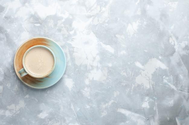 Vista superior xícara de café com leite dentro da xícara na mesa branca beber café leite cor da mesa