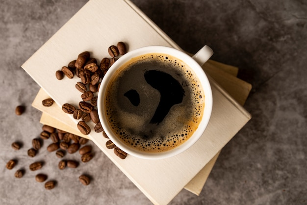 Vista superior xícara de café com livros