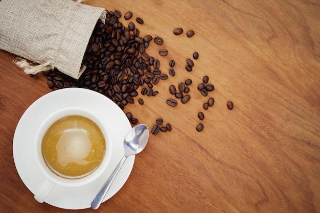 Vista superior, xícara de café e feijão no fundo madeira