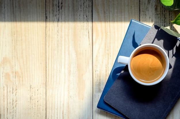 Vista superior xícara de café em livros com espaço de cópia