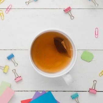 Vista superior xícara de chá com artigos de papelaria