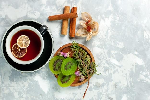 Vista superior xícara de chá com fatias de kiwi e canela na parede branca chá bebida flor limão