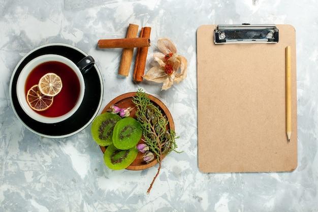 Vista superior xícara de chá com fatias de kiwi e canela na parede branca chá bebida flores limão