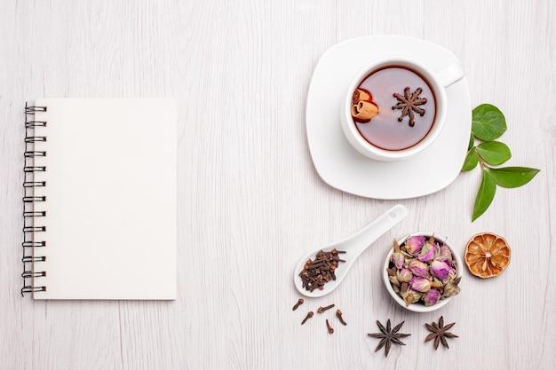 Vista superior xícara de chá com flores e bloco de notas no fundo branco.