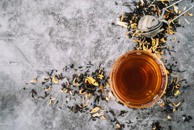 Vista superior xícara de chá com infusor em fundo de mármore