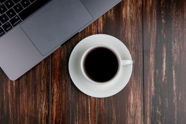 Vista superior xícara de chá com laptop em fundo de madeira