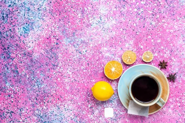 Vista superior xícara de chá com limão na mesa rosa.