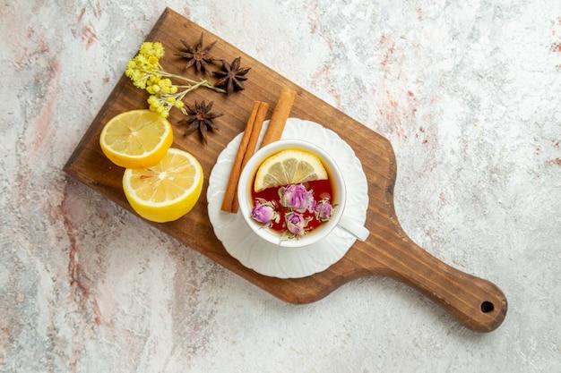 Vista superior xícara de chá com rodelas de limão no fundo branco chá bebida frutas cítricas