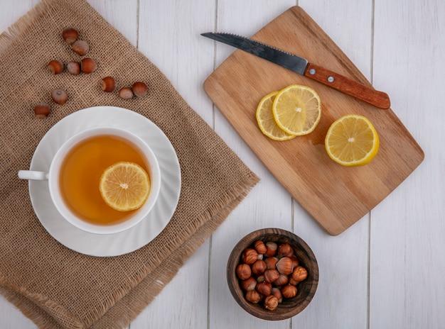 Vista superior xícara de chá com uma fatia de limão em uma placa com uma faca e avelãs em um fundo cinza