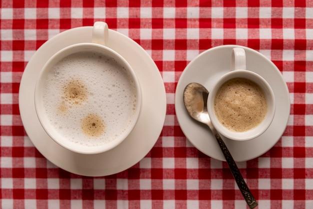 Vista superior xícaras de café com fundo xadrez