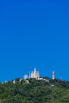 Vista surpreendente à montagem de tibidabo com o parque de diversões na cidade de barcelona.