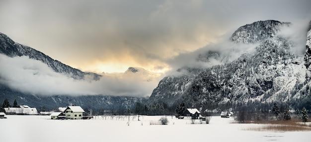 Vista típica da vila pequena dos alpes, dia de inverno nevado.