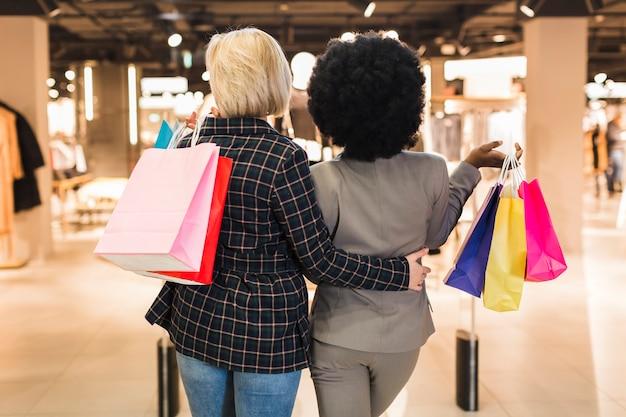 Vista traseira, adulto, mulheres, segurando sacolas compras