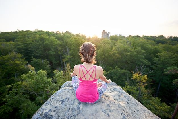 Vista traseira aérea de mulher jovem magro turista sentado na pedra da montanha grande, fazendo yoga ao nascer do sol em árvores verdes tops fundo de floresta