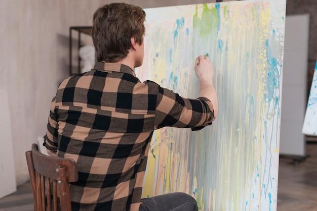 Vista traseira artista homem pintura sobre tela