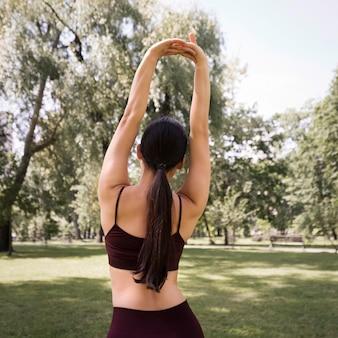 Vista traseira, atlético, mulher, esticar, ao ar livre