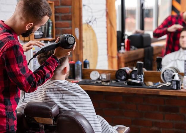Vista traseira barbeiro usando secador de cabelo