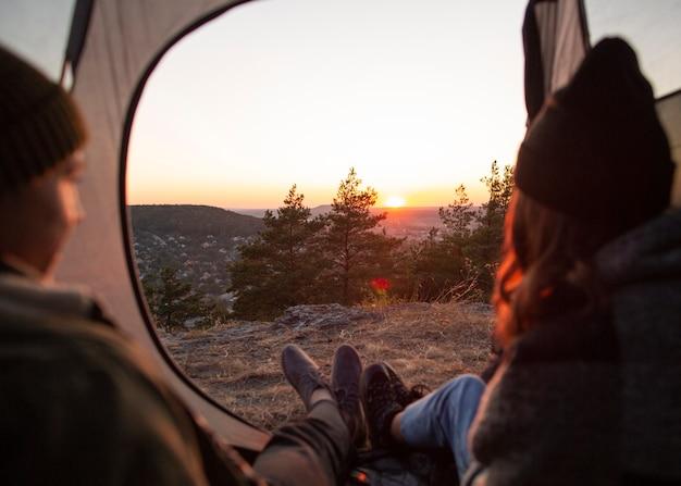 Vista traseira casal apreciando o nascer do sol