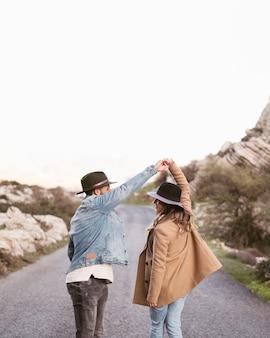 Vista traseira casal caminhando em uma estrada
