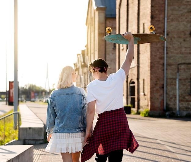Vista traseira casal com skate