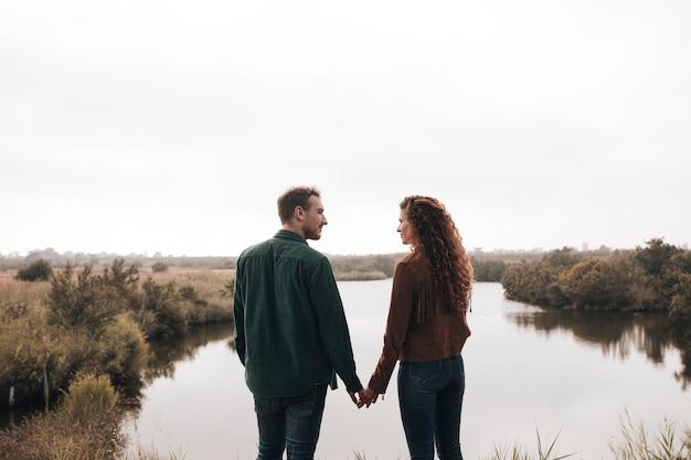 Vista traseira casal de mãos dadas ao lado de uma lagoa