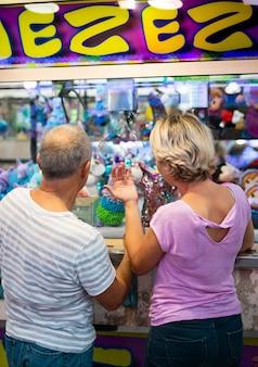 Vista traseira casal na loja de diversões