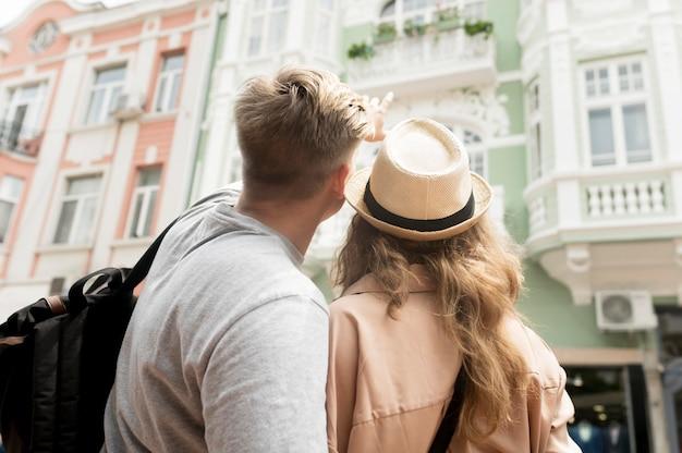 Vista traseira casal olhando para o edifício