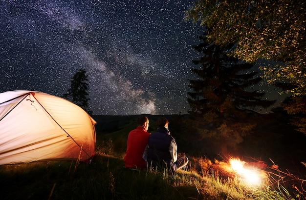 Vista traseira casal romântico turistas descansando no acampamento à noite, sentado junto à fogueira e tenda laranja brilhante perto da floresta num contexto de céu noturno com estrelas e via láctea.