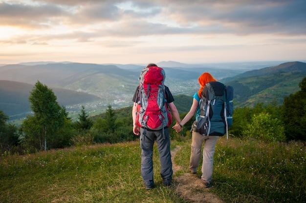 Vista traseira casal turistas com mochilas andando