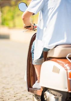Vista traseira cortada imagem de jovem é andar de scooter.