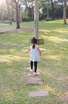 Vista traseira, criança pequena, menina, andar, ligado, pedra, caminho, em, a, jardim, em, a, manhã