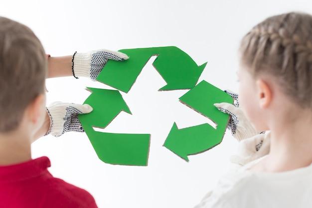 Vista traseira crianças segurando placa reciclar