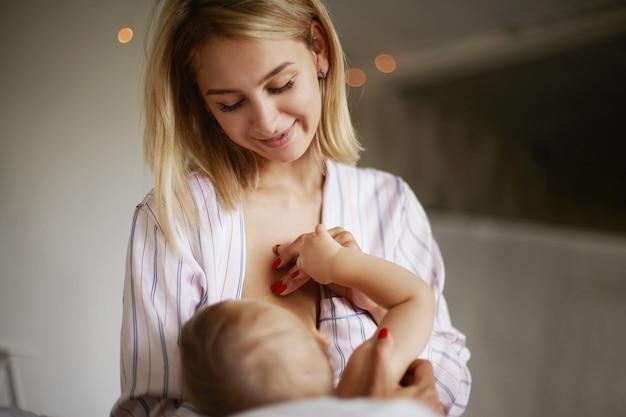 Vista traseira da adorável criança de seis meses bebendo leite materno. atraente jovem europeia com roupas de casa, embalando sua filha nos braços, amamentando-a, desfrutando de uma conexão profunda