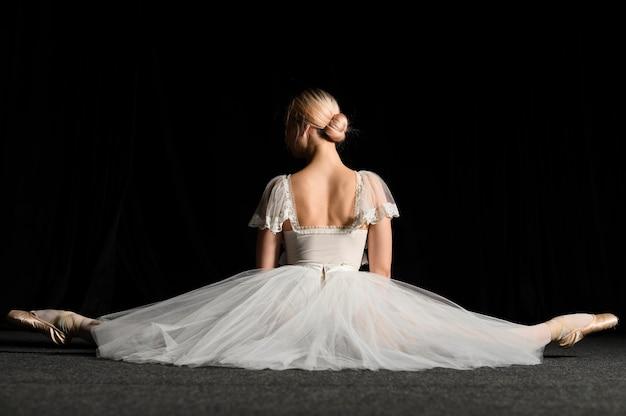 Vista traseira da bailarina com vestido tutu, fazendo uma divisão