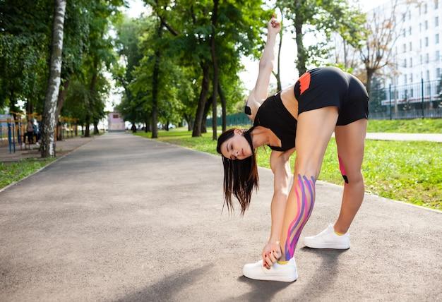 Vista traseira da bruette mulher flexível se aquecendo ao ar livre