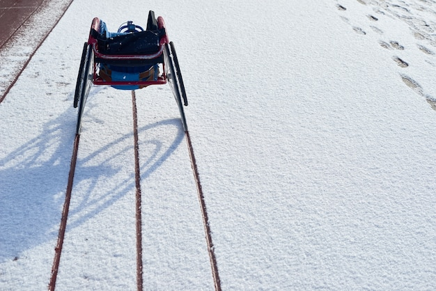 Vista traseira da cadeira de rodas de corrida moderna vazia em pé no estádio de atletismo ao ar livre com vestígios de rodas vistos na neve