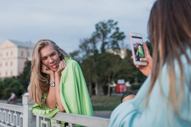 Vista traseira da câmera fotografando uma jovem mulher